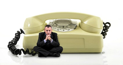 man sitting in front of a giant phone