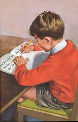 young boy writing a letter at a desk